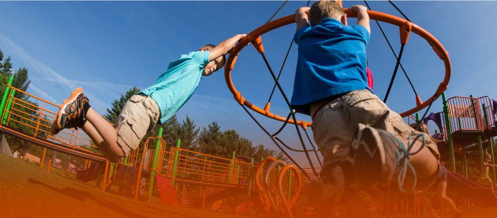 Boys swinging around outdoor playground equipment