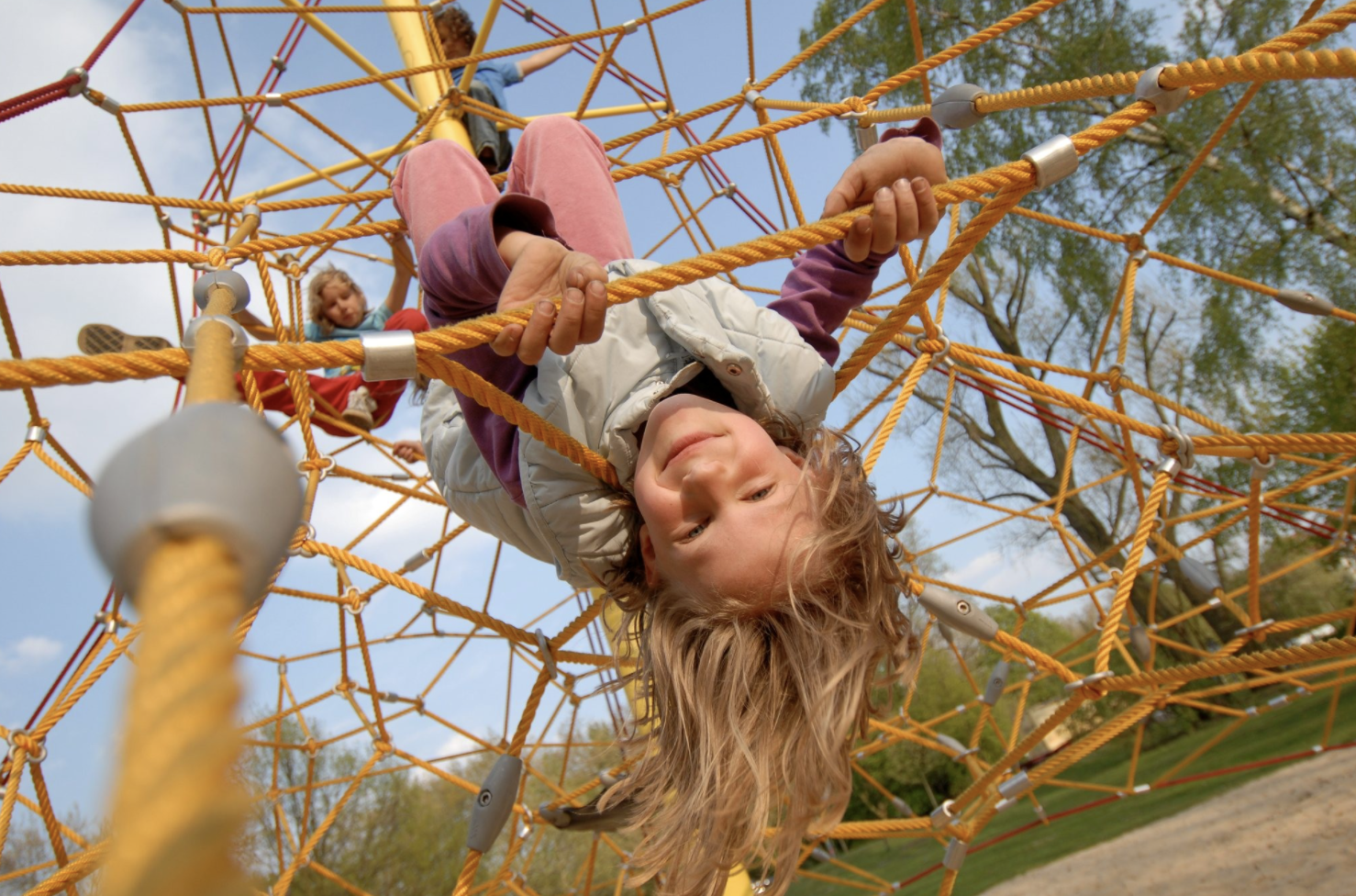 Girl hanging upside down on a rope